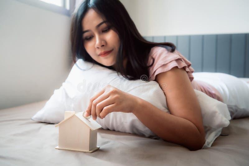 La mano de la mujer del primer está poniendo una moneda del dinero en ahorros de la casa en el dormitorio , La mano femenina está imagen de archivo