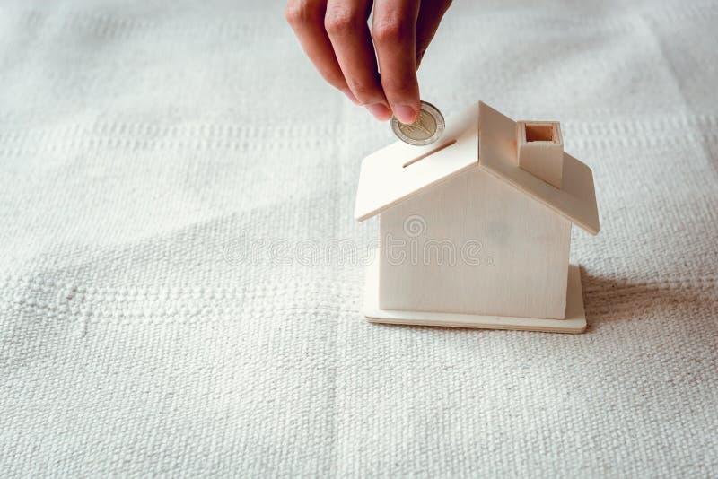 La mano de la mujer del primer está poniendo una moneda del dinero en la vivienda del banco en el dormitorio , La mano femenina e imagen de archivo libre de regalías