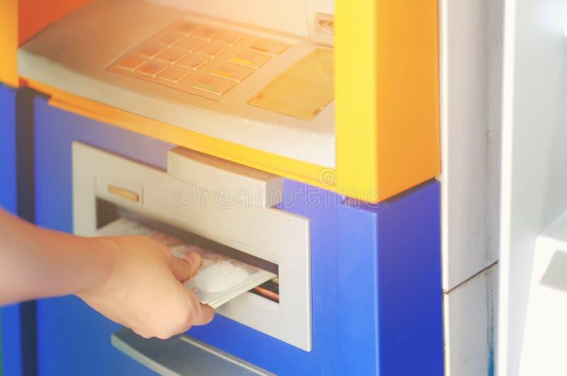 La mano de la mujer del primer que retira el dinero tailandés de la atmósfera del banco, consigue el MES imagenes de archivo