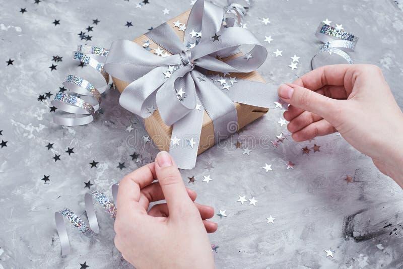La mano de la mujer at? el arco en la caja de regalo foto de archivo libre de regalías