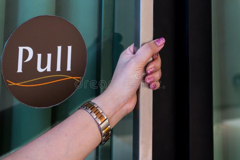 La mano de la mujer está abriendo la puerta fotos de archivo libres de regalías