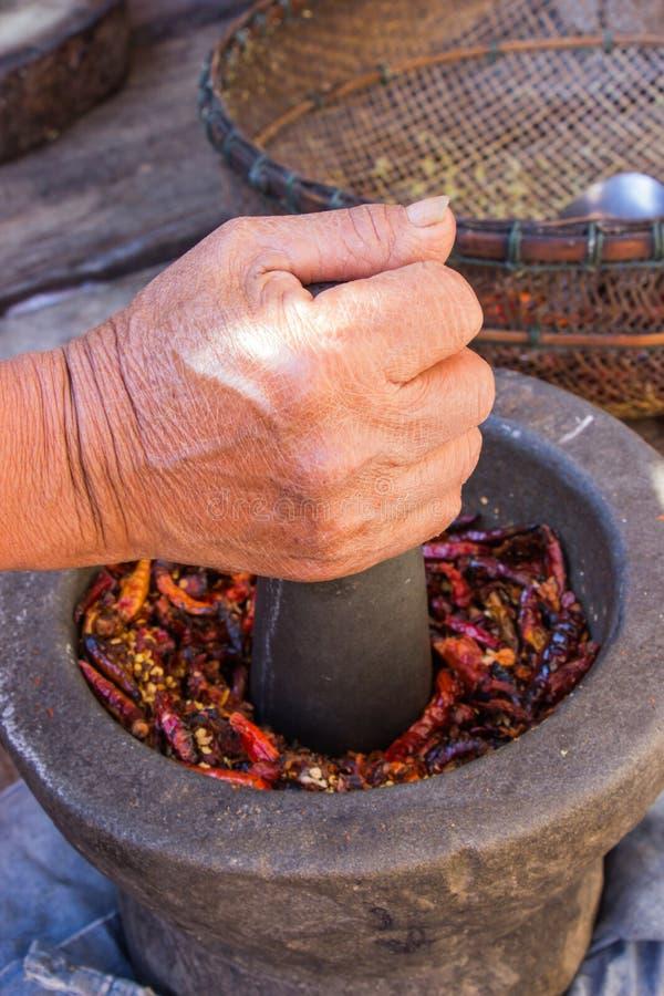 La mano de la mujer está moliendo el chile y el ajo por el mortero y el PE del granito fotos de archivo libres de regalías
