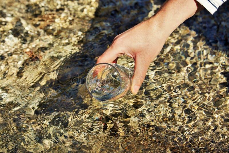 La mano de la mujer está sosteniendo un vidrio de agua imagen de archivo libre de regalías