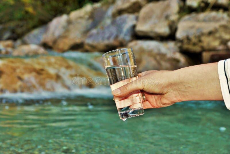 La mano de la mujer está sosteniendo un vidrio de agua fotografía de archivo