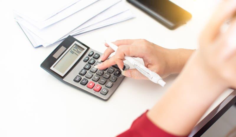 La mano de la mujer está utilizando la calculadora imagen de archivo libre de regalías