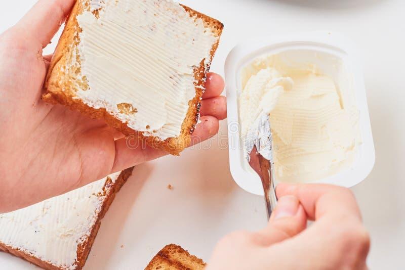 La mano de la mujer hace el bocadillo, pan tostado spred con un queso imagenes de archivo