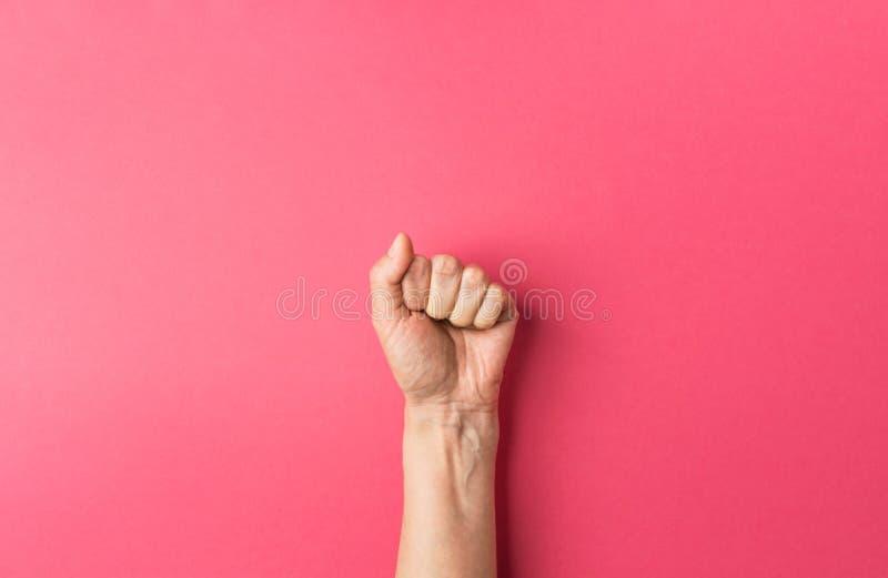 La mano de la mujer joven del caucásico con el puño apretado en fondo rosado fucsia Igualdad de la libertad de la independencia d foto de archivo