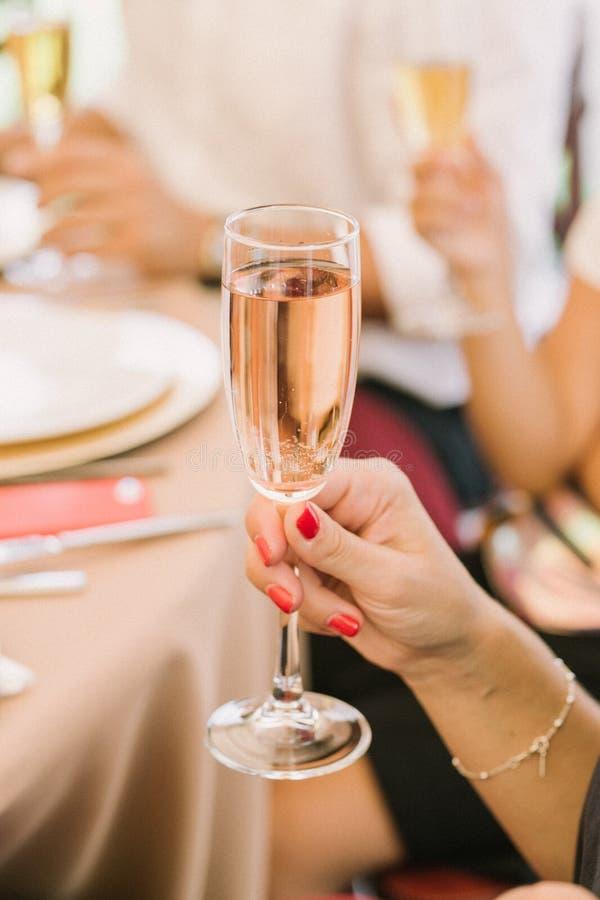 La mano de la mujer lleva a cabo el vidrio de champaigne Foco en la copa de vino imagen de archivo libre de regalías