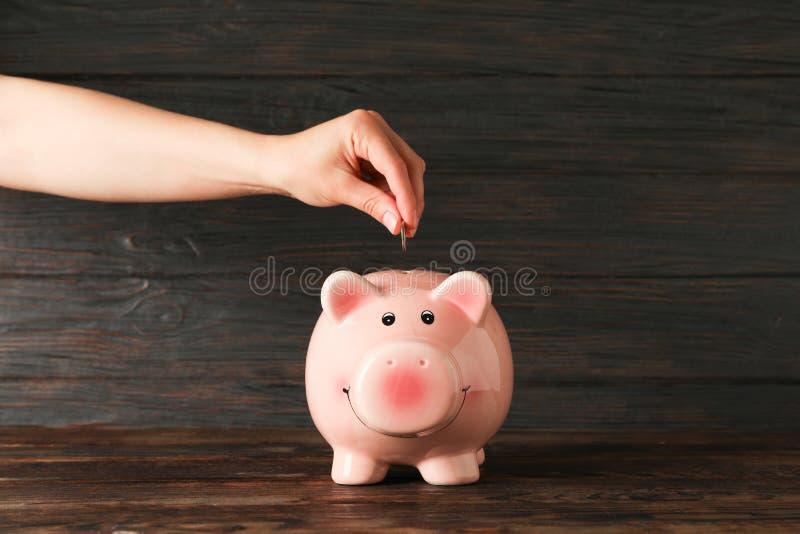 La mano de la mujer pone una moneda en la hucha feliz en la tabla de madera contra el fondo de madera, espacio para el texto imágenes de archivo libres de regalías