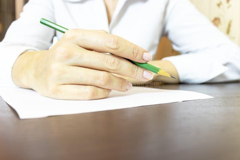 La mano de la mujer que describe algo en cierre del papel Mujer de negocios irreconocible en la escritura blanca de la camisa con fotos de archivo libres de regalías