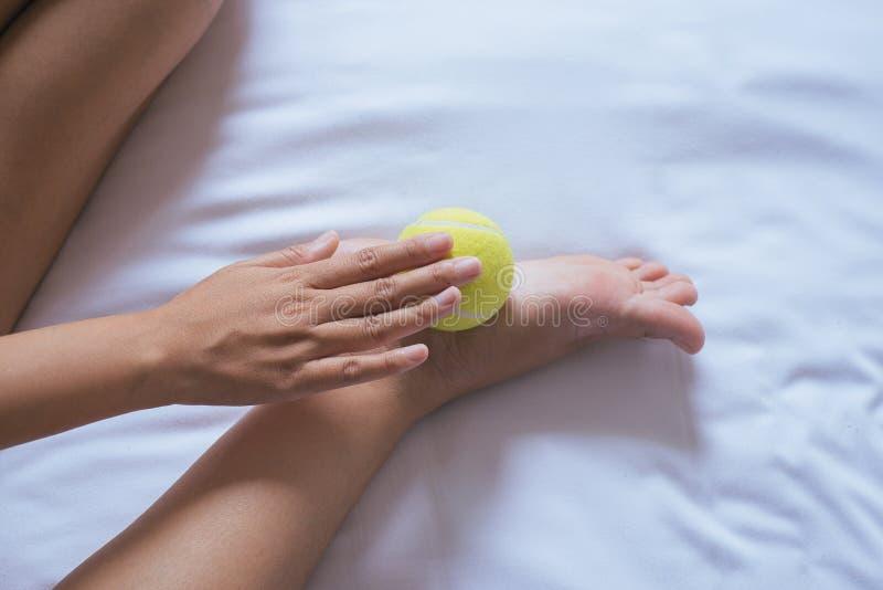 La mano de la mujer que le da masaje con la pelota de tenis se alza en el dormitorio, masaje de los lenguados del pie fotos de archivo