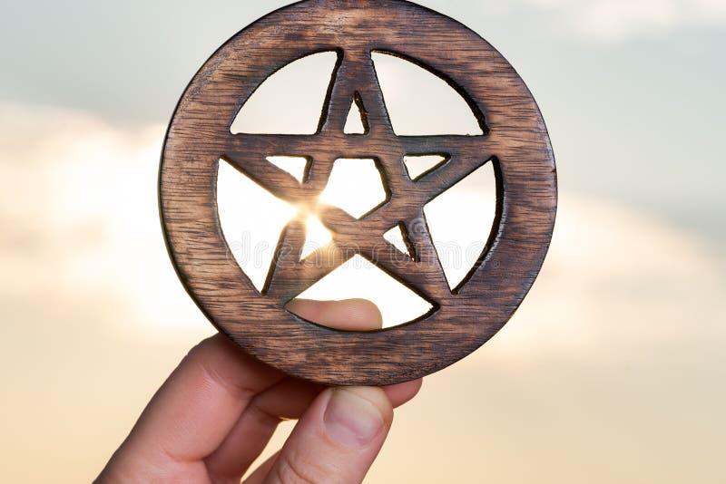 La mano de la mujer que lleva a cabo símbolo cercado de madera del Pentagram en la salida del sol delante del lago Concepto de ci imágenes de archivo libres de regalías