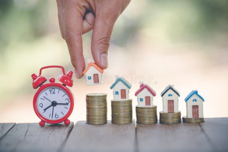 La mano de la mujer que pone el modelo de la casa en pila de las monedas Concepto para la escalera de la propiedad, dinero de pla imágenes de archivo libres de regalías