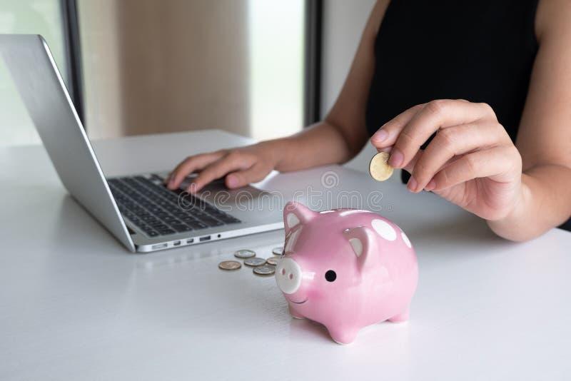 La mano de la mujer que pone la moneda de oro en la hucha y el ordenador portátil rosados del uso para el márketing en línea, int fotografía de archivo