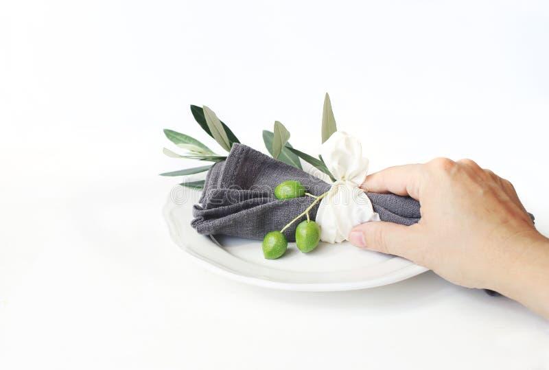 La mano de la mujer que sostenía la servilleta de lino gris decoted por la cinta de la rama de olivo y de la seda Ajuste festivo  foto de archivo