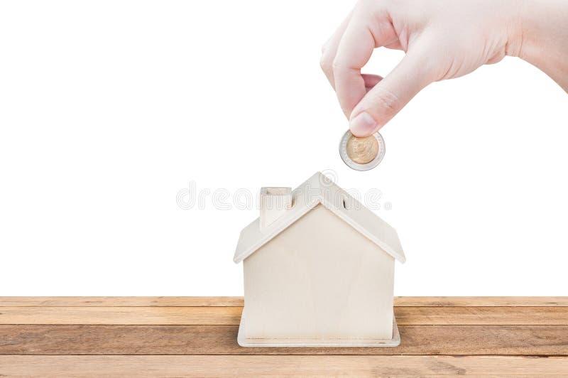 La mano de la mujer que sostiene el banco de la casa de las monedas ahorra el dinero aislado en el fondo blanco fotografía de archivo libre de regalías
