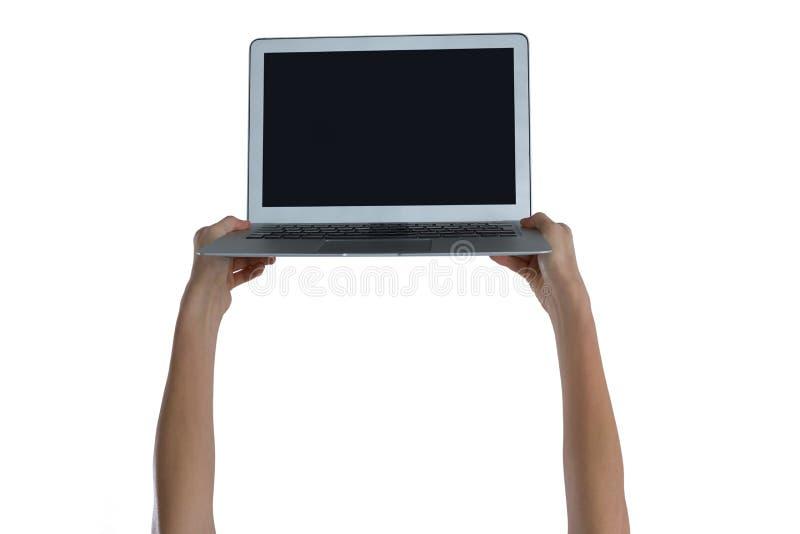 La mano de la mujer que sostiene el ordenador portátil fotografía de archivo