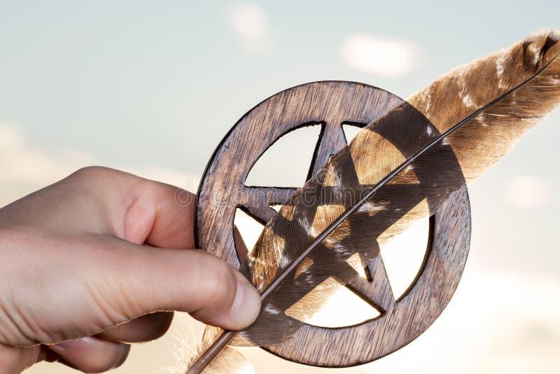 La mano de la mujer que sostiene símbolo cercado de madera del Pentagram y la pluma de Turquía en la salida del sol Concepto de c fotos de archivo libres de regalías