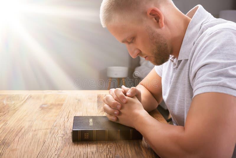 La mano de rogaci?n del hombre en la biblia foto de archivo libre de regalías