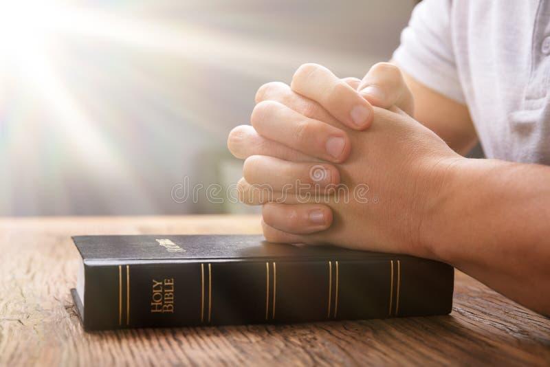 La mano de rogaci?n del hombre en la biblia fotos de archivo libres de regalías