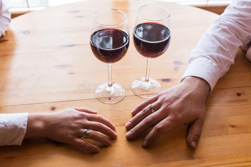 La mano de un hombre con un anillo estira a la mano del ` s de la mujer Dos vidrios con el vino rojo Cena romántica, una fecha imagen de archivo
