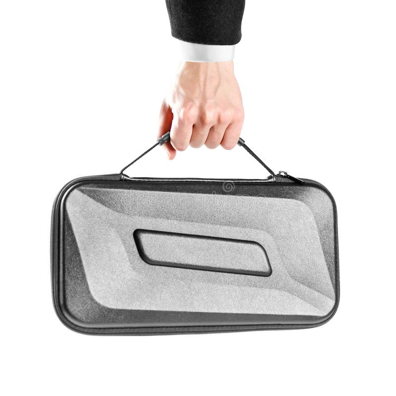 La mano de un hombre en la camisa blanca y la chaqueta negra sostiene una maleta plástica negra Cierre para arriba Aislado en el  fotografía de archivo libre de regalías