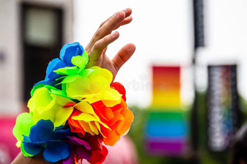 La mano de un hombre en el aire con una pulsera del arco iris en el desfile de Gay Pride foto de archivo libre de regalías