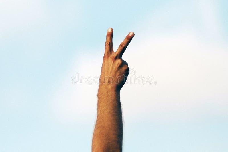 La mano de un hombre musulm?n que muestra una muestra del peece imagenes de archivo