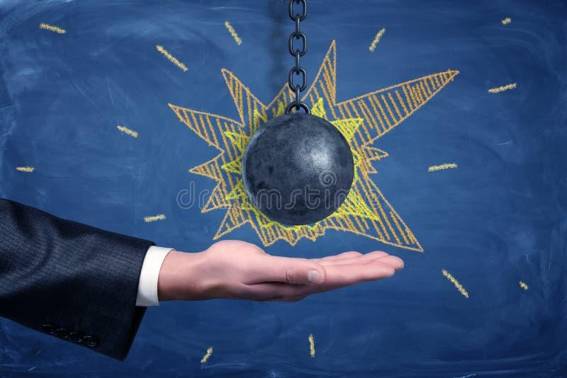 La mano de un hombre de negocios con un hierro negro que arruina la bola con explosiones tiza-dibujadas alrededor de ella imágenes de archivo libres de regalías