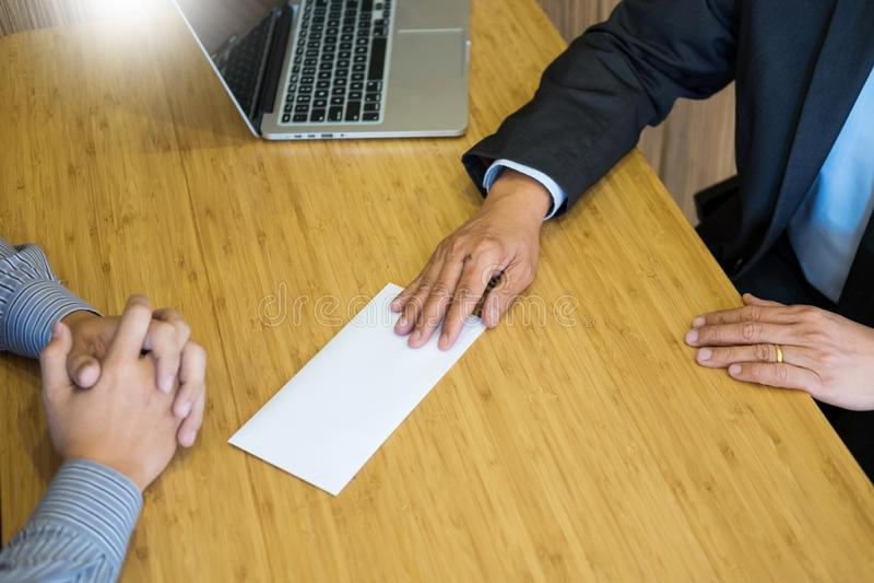 La mano de un hombre de negocios entrega una remuneración final de la carta de dimisión al jefe ejecutivo en una tabla de madera  fotos de archivo
