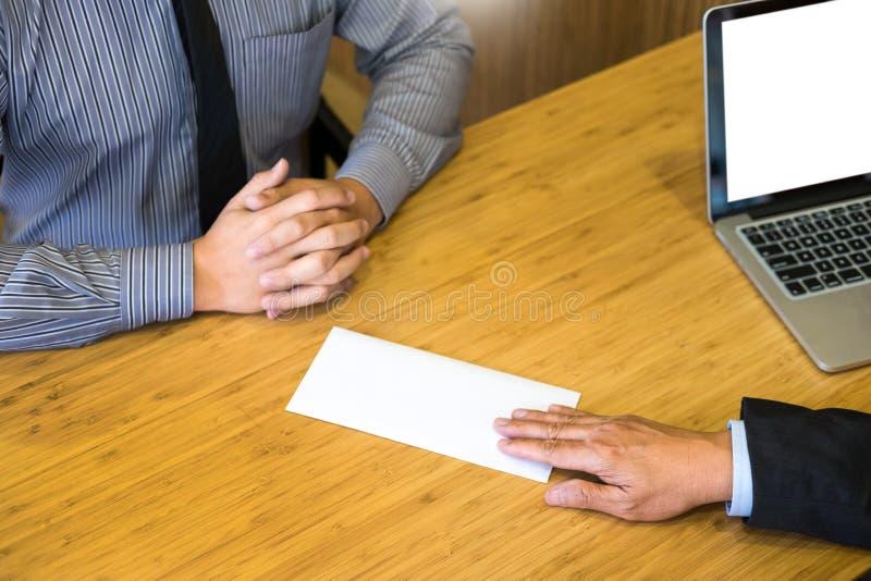 La mano de un hombre de negocios entrega una remuneraci?n final de la carta de dimisi?n al jefe ejecutivo en una tabla de madera  fotos de archivo