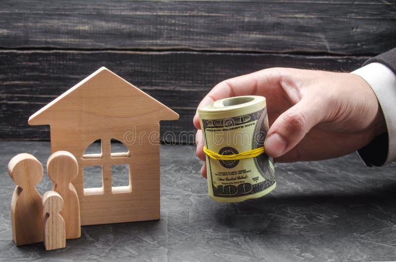 La mano de un hombre de negocios extiende el dinero a una casa de madera La familia se está colocando cerca de la casa El concept imagen de archivo