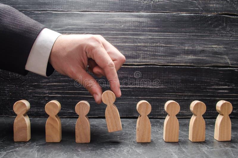 la mano de un hombre de negocios toma una figura de madera de un hombre El concepto de trabajadores de la búsqueda, del alquiler  foto de archivo