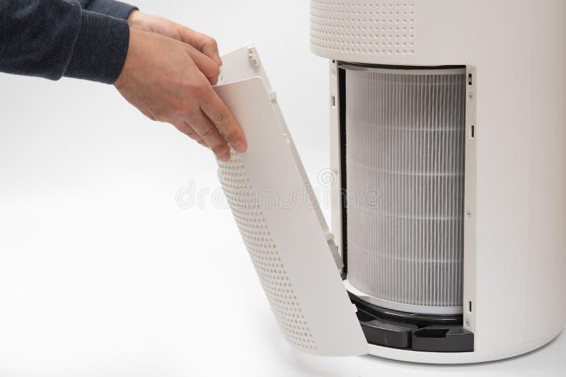 La mano de un hombre que da vuelta al filtro de un purificador del aire en un nuevo fotos de archivo