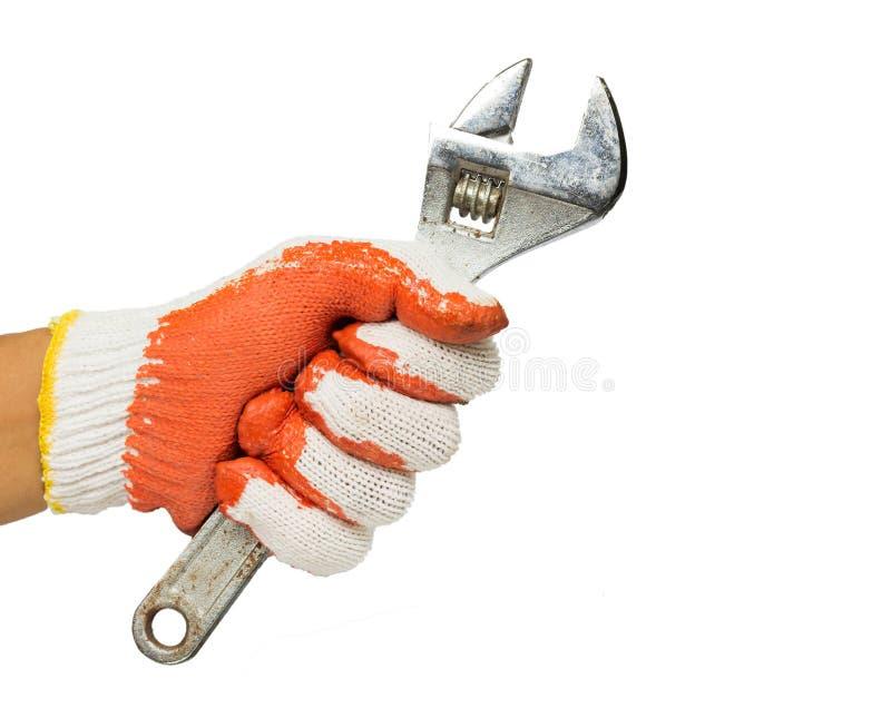 La mano de un hombre que sostiene la llave ajustable aislada en el fondo blanco Mec?nico y reparador handyman DIY fotos de archivo