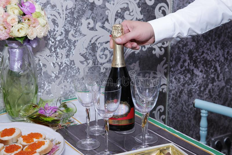 La mano de un hombre sostiene una botella de champán en una tabla servida con los vidrios de bocadillos con el caviar rojo fotos de archivo