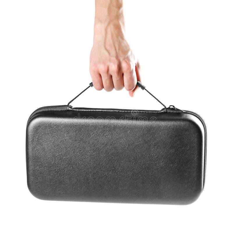La mano de un hombre sostiene una maleta plástica negra Cierre para arriba Aislado en el fondo blanco imagen de archivo