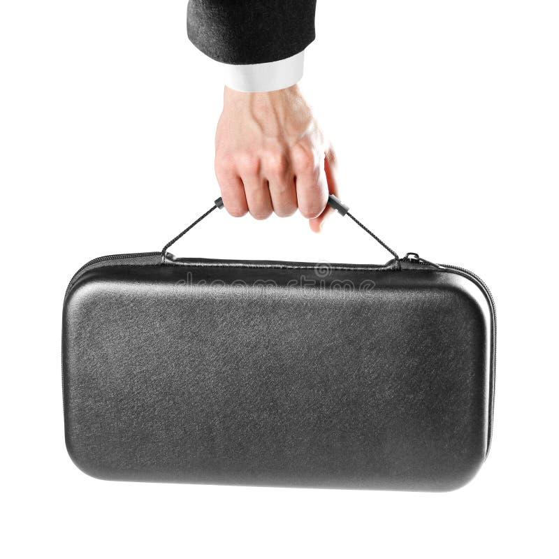 La mano de un hombre sostiene una maleta plástica negra Cierre para arriba Aislado en el fondo blanco fotos de archivo libres de regalías