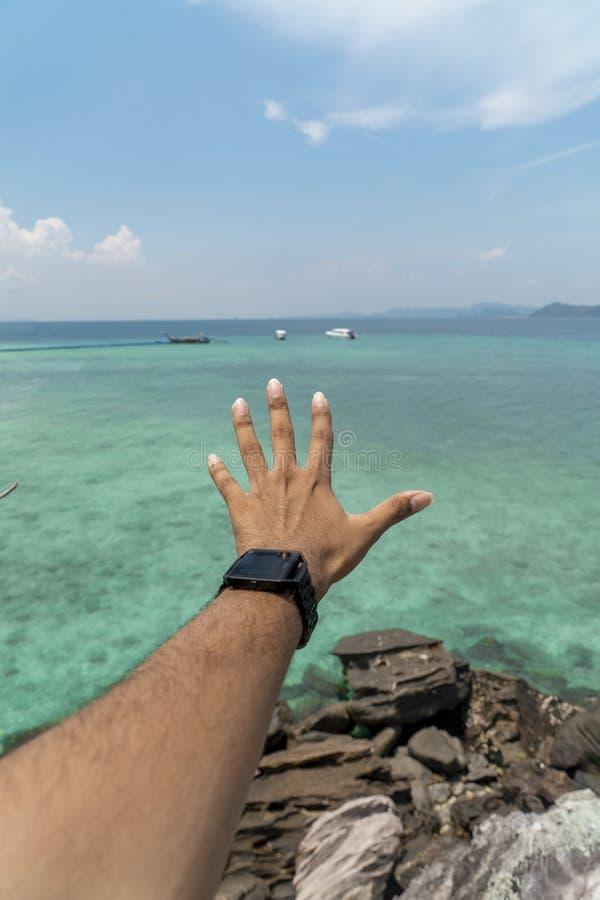 La mano de un varón que alcanza al mar fotografía de archivo