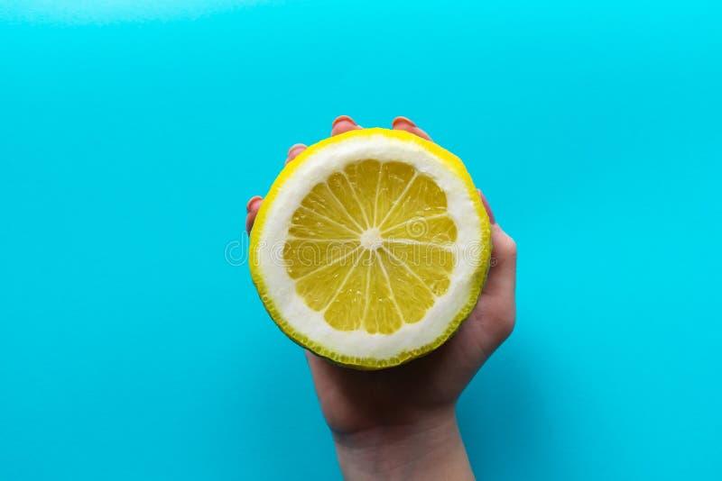 La mano de una muchacha sostiene un medio limón grande en un fondo azul Opinión superior puesta plana del primer foto de archivo