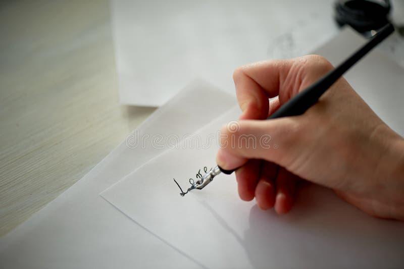 La mano de una mujer escribe con la tinta, una pluma Escritura El proceso creativo de crear un trabajo, el amor de la palabra imagen de archivo