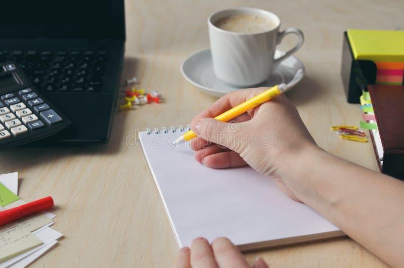 La mano de una mujer está sosteniendo una pluma negra en el primer del escritorio Estudio y y concepto de trabajo foto de archivo