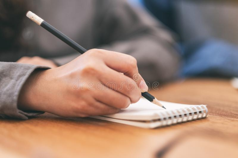La mano de una mujer que escribe en el cuaderno en blanco en la tabla de madera imágenes de archivo libres de regalías
