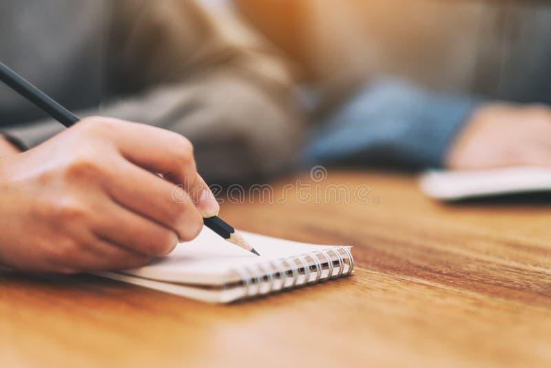 La mano de una mujer que escribe en el cuaderno en blanco en la tabla de madera fotos de archivo libres de regalías