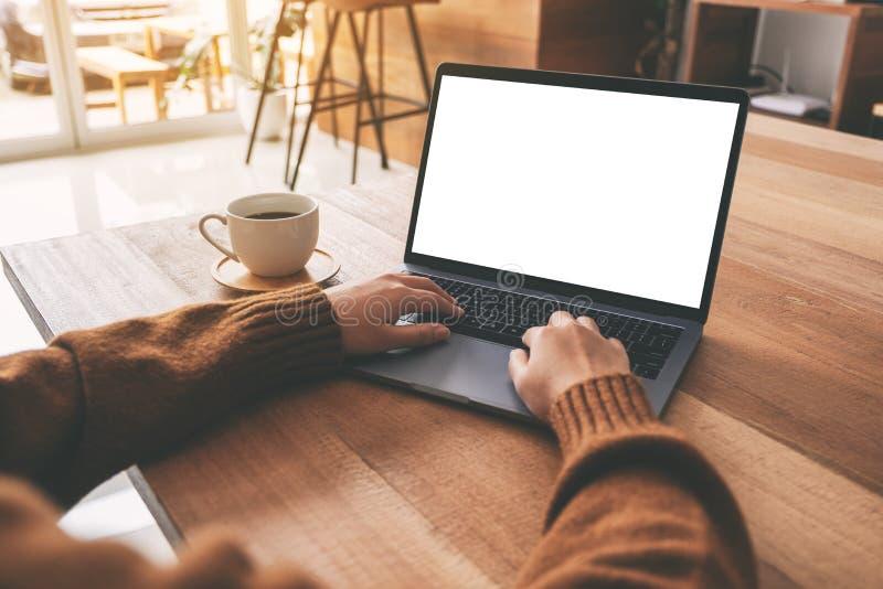La mano de una mujer usando y mecanografiando en el ordenador portátil con la pantalla de escritorio blanca del espacio en blanco imagen de archivo libre de regalías