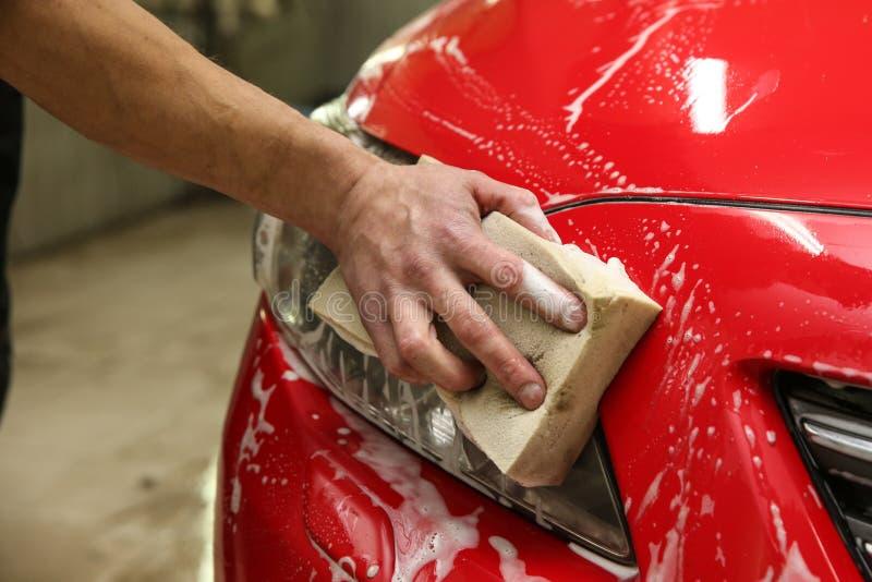 La mano de Washerman est? lavando el coche por cierre de la esponja para arriba foto de archivo libre de regalías