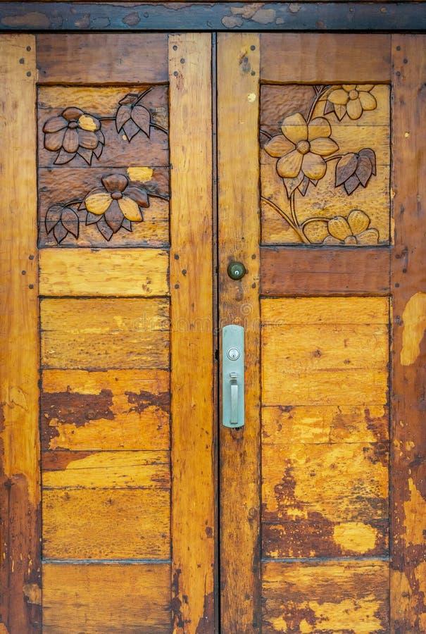 La mano decorata ha scolpito la vecchia porta di legno verniciata pesante con progettazione del fiore del corniolo fotografia stock