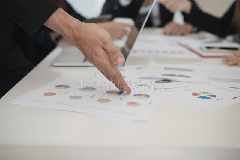 La mano degli uomini d'affari indica per rappresentare graficamente mentre gruppo che discute sullo sto immagini stock
