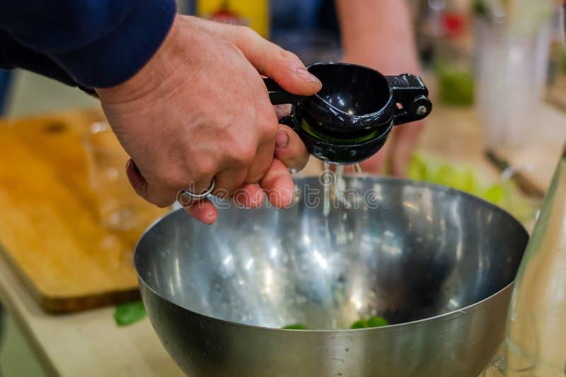 La mano degli uomini facendo uso dello spremitoio del limone al limone del succo in una ciotola del metallo fotografia stock