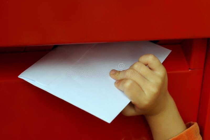 La mano dei bambini che mette lettera nella cassetta delle lettere fotografia stock libera da diritti